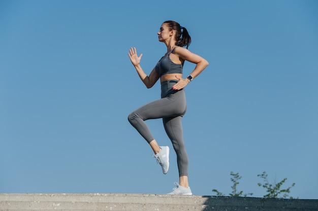 Widok z boku na brunetkę ćwiczącą na świeżym powietrzu pod błękitnym, czystym niebem