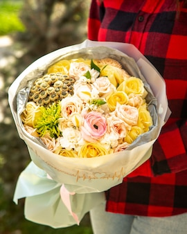 Widok z boku na bukiet różowych róż z różowymi kwiatami jaskier i chryzantemy santini