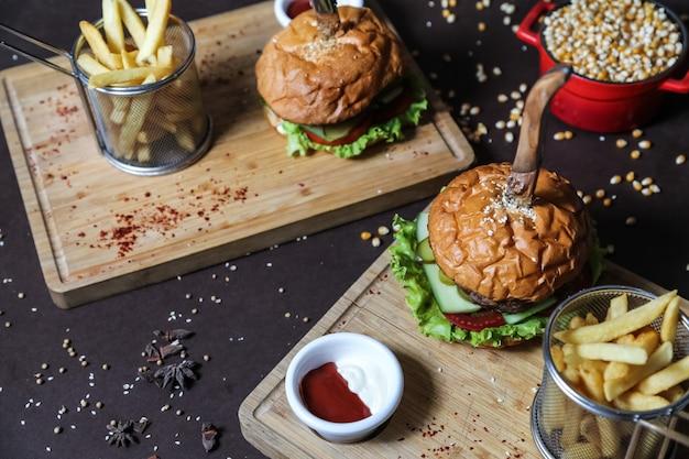Widok z boku na burgery z frytkami, keczupem i majonezem na stojakach z nożami