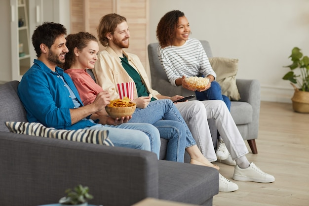 Widok z boku na całej długości na wieloetniczną grupę przyjaciół, którzy razem oglądają telewizję, siedząc na wygodnej kanapie w domu i delektując się przekąskami