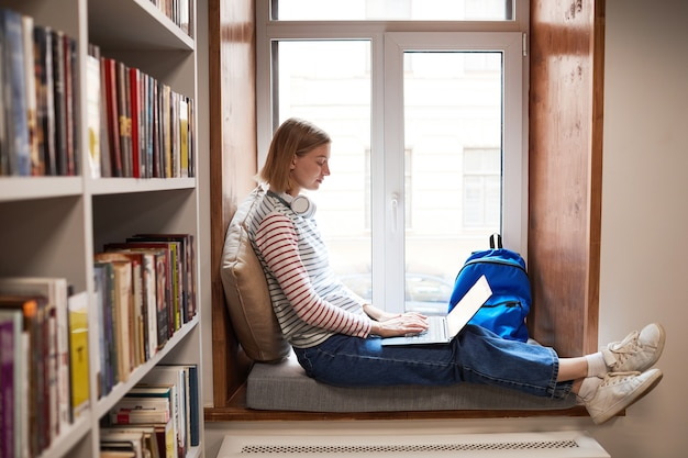Widok z boku na całej długości portret młodej kobiety relaksującej się przy oknie w czytelni w bibliotece kopii s...