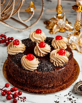 Widok z boku na ciasto czekoladowe z bitą śmietaną i wiśniami na stole