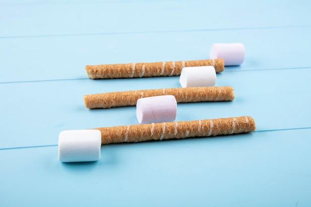 Widok z boku na cukierki i chrupiące paluszki na niebieskim tle