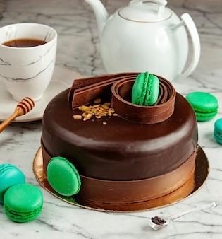 Widok z boku na czekoladowe ciasto udekorowane zielonymi makaronikami podawane z herbatą na stole