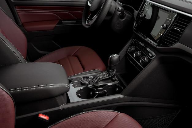 Widok z boku na deskę rozdzielczą luksusowego samochodu, czerwone skórzane fotele, automatyczną skrzynię biegów, kierownicę i ekran dotykowy