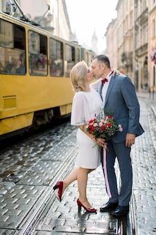 Widok z boku na dojrzałą parę przytulającą się i całującą podczas spaceru po pięknym starym mieście