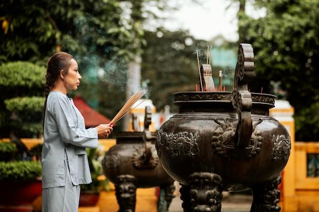Widok z boku na duchową kobietę z płonącą kadzidłem w świątyni
