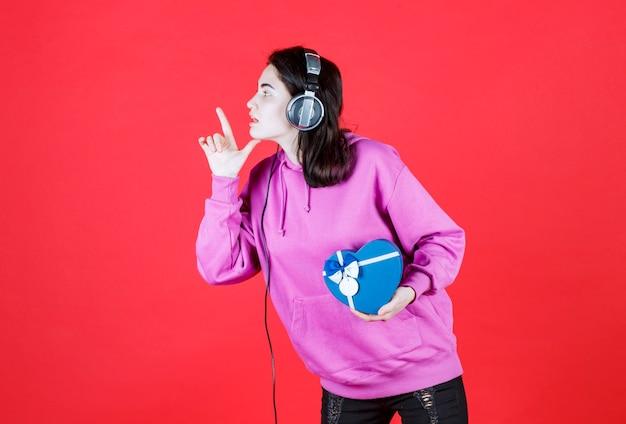 Widok z boku na dziewczynę, która robi znak ręką i patrząc w jej prawą stronę, trzymając pudełko