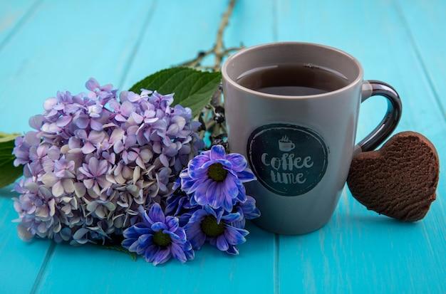 Widok z boku na filiżankę herbaty z pięknymi kwiatami na białym tle na niebieskim tle drewnianych