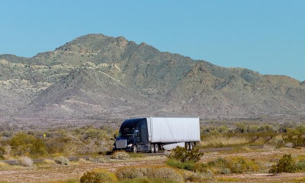 Widok z boku na flotę jasnych, dużych ciężarówek, przewożących ładunki w długiej naczepie na płaskiej drodze w górach usa