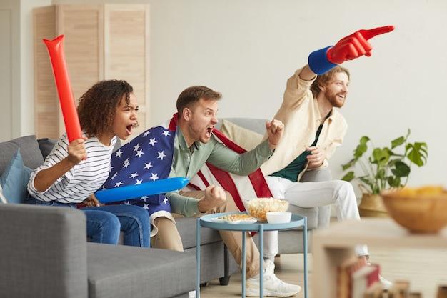 Widok z boku na grupę młodych ludzi oglądających mecz w telewizji w domu i wiwatujących emocjonalnie, mając na sobie amerykańską flagę