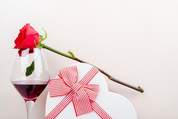 Widok z boku na kieliszek wina czerwonego koloru róży i pudełko w kształcie serca związane z kokardą na białym tle