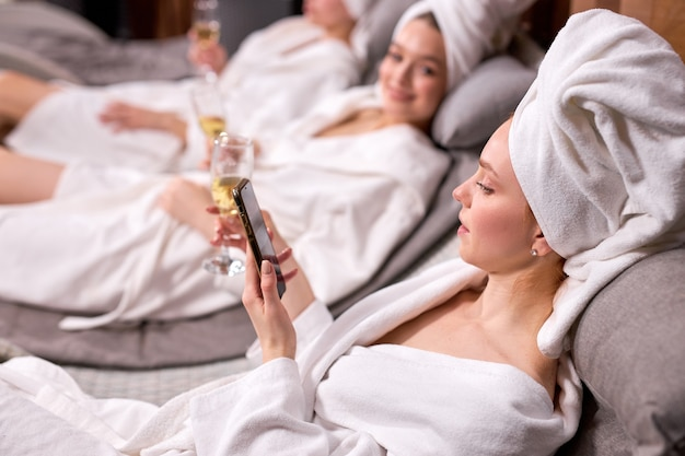 Widok z boku na kobietę w salonie spa pije szampana i surfuje po sieci, używając smartfona po zabiegach kosmetycznych w spa