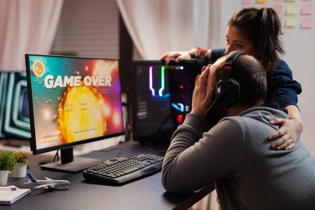 Widok z boku na koniec gry dla pary profesjonalnych graczy, grających w kosmiczne strzelanki. pokonany mężczyzna streamujący cybernetykę online podczas turnieju gier