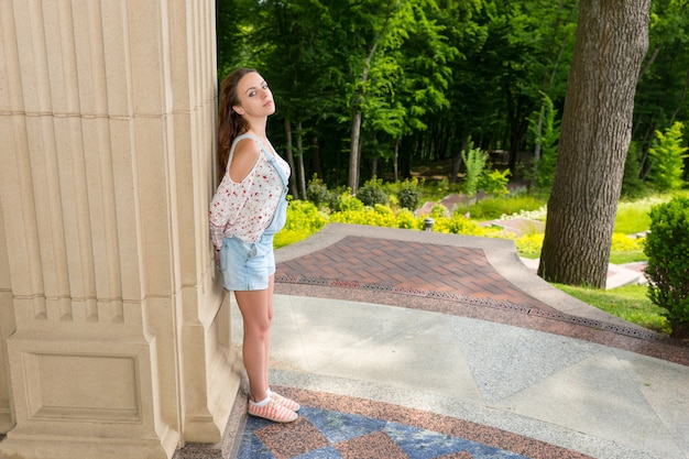 Widok z boku na kontemplacyjną młodą dorosłą kobietę stojącą w pobliżu kamiennej ściany i patrzącą w kamerę na zewnątrz, z widokiem na drzewa w parku lub na podwórku
