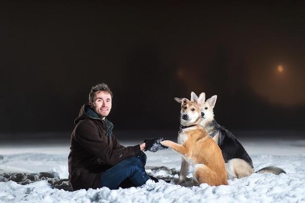 Widok z boku na mężczyznę siedzącego przed dwoma psami rasy mieszanej w nocy zimą gdzieś na północy