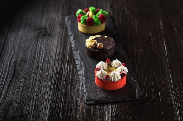 Widok z boku na mini party tartlets ze świeżymi owocami, czekoladą, orzechami i śmietaną na czarnym tle łupków. słodkie ciasta