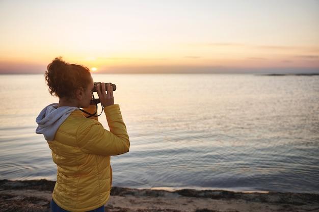 Widok z boku na młodą kobietę w żółtej kurtce patrzącą przez lornetkę i podziwiającą piękny widok na nadmorski krajobraz