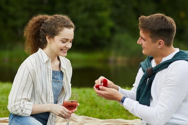 Widok z boku na młodego mężczyznę otwierającego pudełko na pierścionek, proponując dziewczynie podczas romantycznej randki na świeżym powietrzu