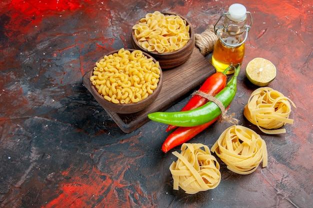 Widok z boku na niegotowane makarony, papryki cayenne związane ze sobą sznurkiem butelka oleju cytrynowy czosnek na stole o mieszanych kolorach
