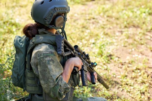 Widok z boku na nierozpoznawalną kobietę w wojskowym stroju siedzącą na trawie, czekającą na wroga z boku