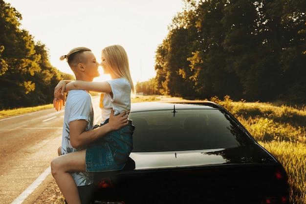 Widok z boku na niesamowitą parę przytulającą się, podczas gdy kobieta siedzi z tyłu swojego samochodu na poboczu drogi podczas podróży przed zachodem słońca.