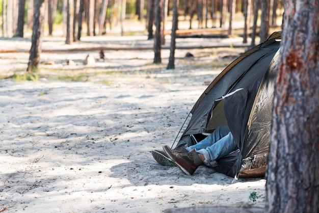Widok z boku na nogi mężczyzny na zewnątrz namiotu