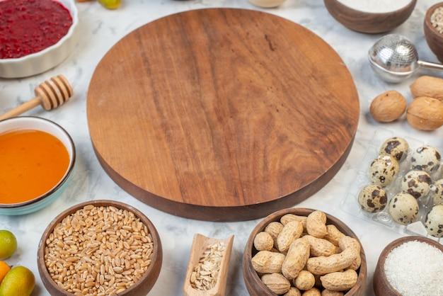 Widok z boku na okrągłą drewnianą deskę wśród jajek z dżemem z mąki, brązowy ryż na lodowym tle