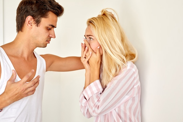 Widok z boku na okrutnego mężczyznę zbesztającego żonę w domu w jasnym pokoju, konflikt rodzinny i obraźliwe toksyczne związki
