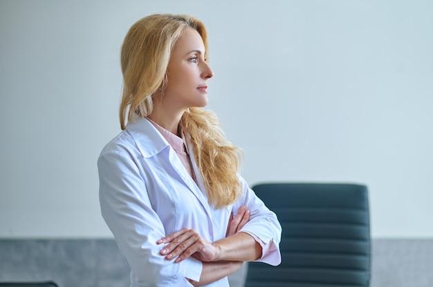 Widok z boku na piękną spokojną, zamyśloną profesjonalną kobietę otolaryngologa z założonymi rękoma, patrzącą w dal