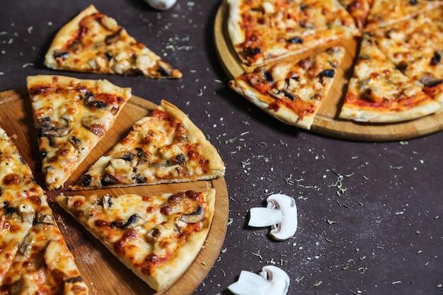 Widok z boku na pizzę na blachach z pieczarkami i przyprawami