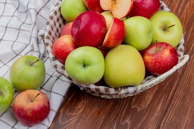 Widok z boku na pokrojone i całe jabłka w koszu i na kraciastej szmatce na powierzchni drewnianych