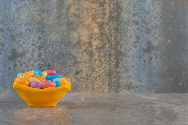 Widok z boku na pomarańczową miskę pełną cukierków żelowych.