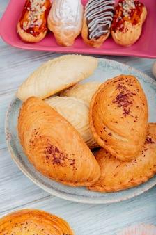 Widok z boku na produkty piekarnicze, jak badambura shakarbura goghal w talerzu z ciasta na powierzchni drewnianych