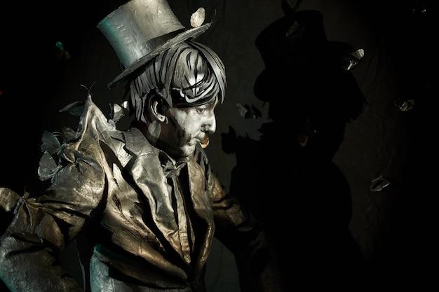 Widok z boku na profesjonalnego pantomimistę w pomalowanym garniturze i kapeluszu, stojącego nieruchomo z czarną ścianą za plecami i latającymi sztucznymi motylami. artysta pokazujący swoje umiejętności improwizacji