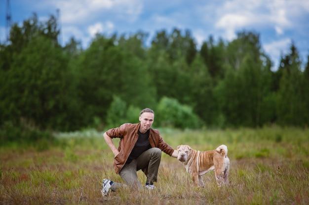 Widok z boku na psa rasy shar pei z właścicielem na spacerze w polu. zielona trawa i błękitne niebo pochmurne