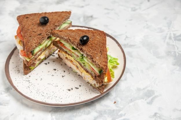 Widok z boku na pyszną kanapkę z czarnym chlebem ozdobionym oliwką na talerzu na poplamionej białej powierzchni
