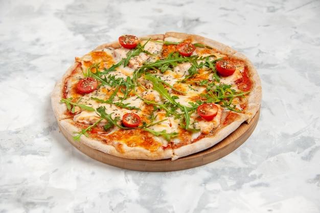 Widok z boku na pyszną pizzę z zielenią pomidorów na poplamionej białej powierzchni