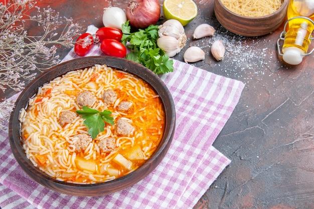 Widok z boku na pyszną zupę z kurczaka z zielonymi makaronami i łyżką na różowym ręczniku butelka oleju z czosnkiem pomidory cytryna na ciemnym tle