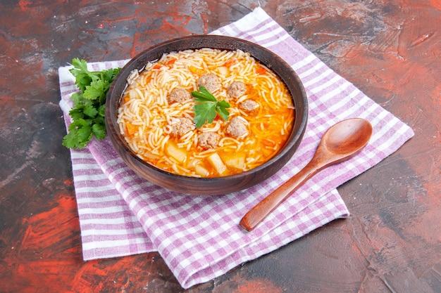 Widok z boku na pyszną zupę z kurczaka z zielonymi makaronami i łyżką na różowym ręczniku w paski na ciemnym tle