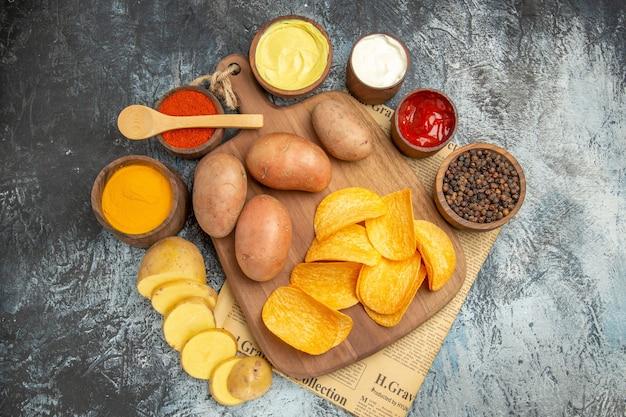 Widok z boku na pyszne domowe chipsy ziemniaczane i różne przyprawy majonezowy sos kethup na gazecie