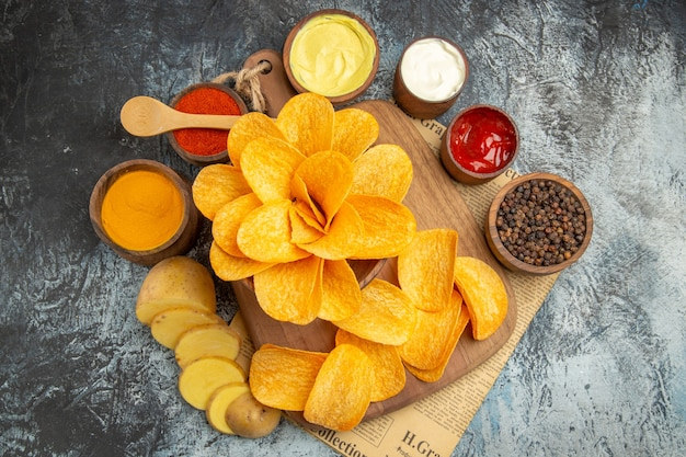 Widok z boku na pyszne domowe chipsy ziemniaczane na drewnianej desce do krojenia różne przyprawy i keczup majonezowy w gazecie na szarym stole