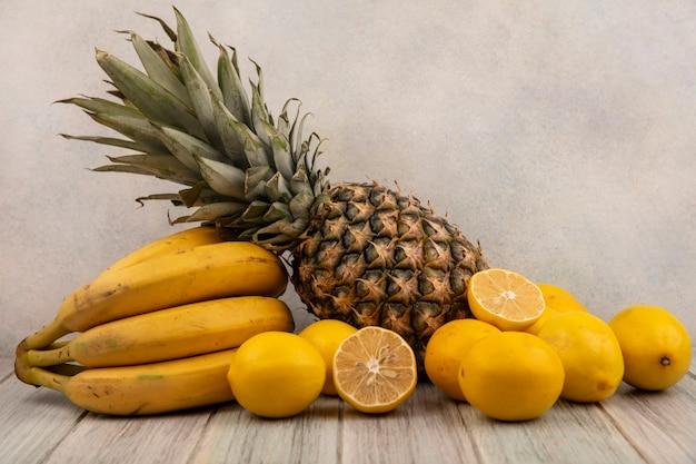 Widok z boku na pyszne owoce, takie jak banany, ananasy i cytryny na białym tle na szarym tle