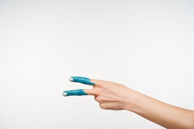 Widok z boku na rękę eleganckiej damy z niebieskim kolorem tworzącym gest pokoju dwoma palcami podczas pozowania na biało. znaki dłoni i koncepcja gestykulacji
