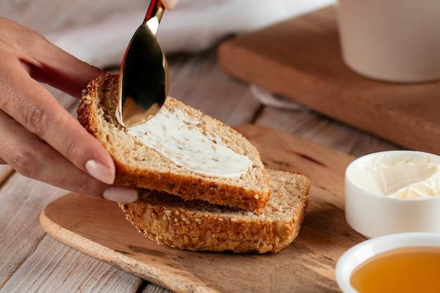 Widok z boku na rozkładanie kromki chleba z masłem