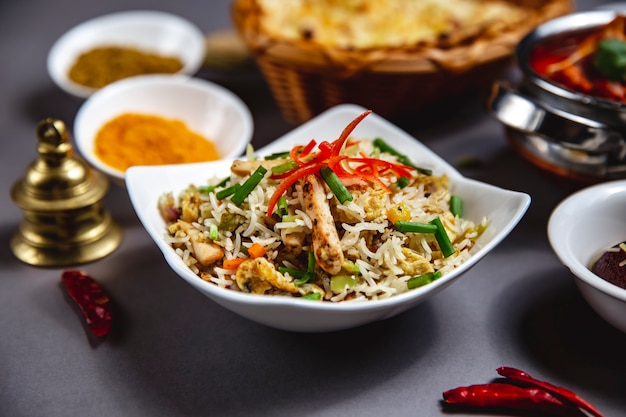 Widok z boku na ryż ozdobiony grillowanym kurczakiem, ogórkiem, marchewką i papryką