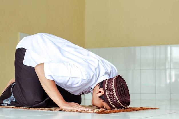 Widok z boku na salat muzułmanina z pokłonem na macie modlitewnej