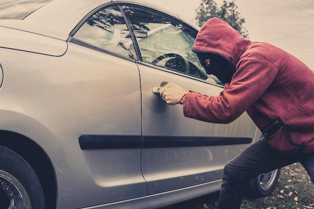 Widok z boku na samochód zmuszany przez mężczyznę w bluzie z kapturem i masce. złodziej próbuje ukraść pojazd z parkingu. młody mężczyzna działa samotnie łamiąc drzwi samochodu. nieznana osoba otwiera samochód. oszustwa samochodowe.