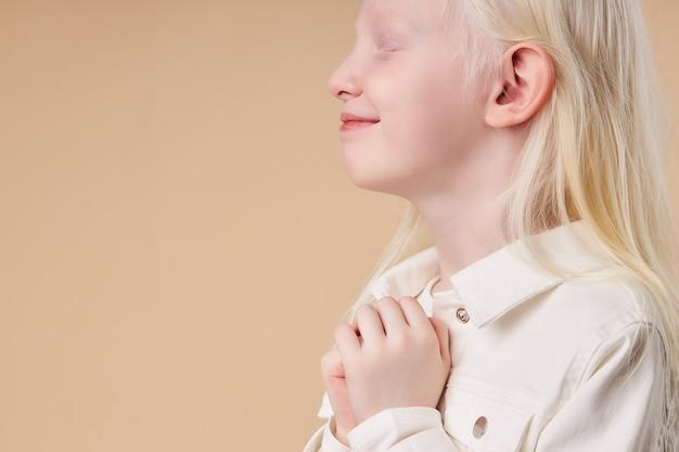 Widok z boku na słodkie dziecko albinos w oczekiwaniu na prezent