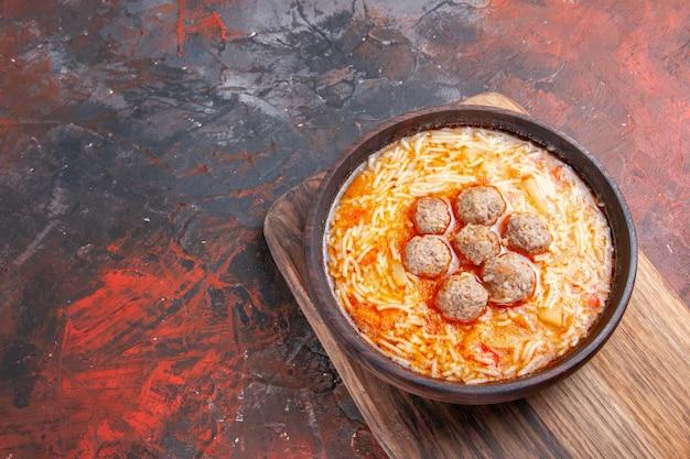 Widok z boku na smaczną zupę z klopsików z makaronem na drewnianej desce do krojenia na ciemnym tle
